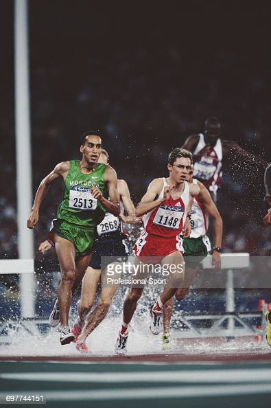 View of Brahim Boulami of Morocco in competition with Gunther Weidlinger of Austria as they cross the water jump during the final of the Men's 3000...