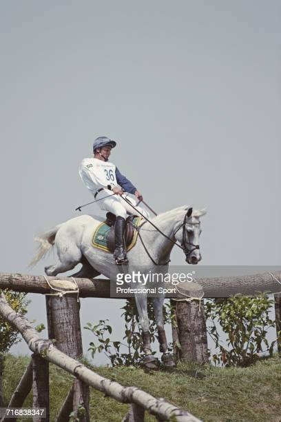 View of Brazilian equestrian Serguei Fofanoff of the Brazil team riding Kaiser Eden negotiating a wooden hazard and grass slope during competition in...
