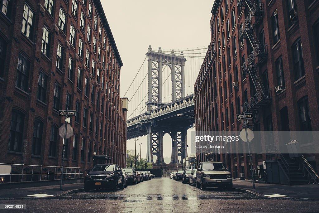 View of Brooklyn Bridge between industrial buildings, New York, USA