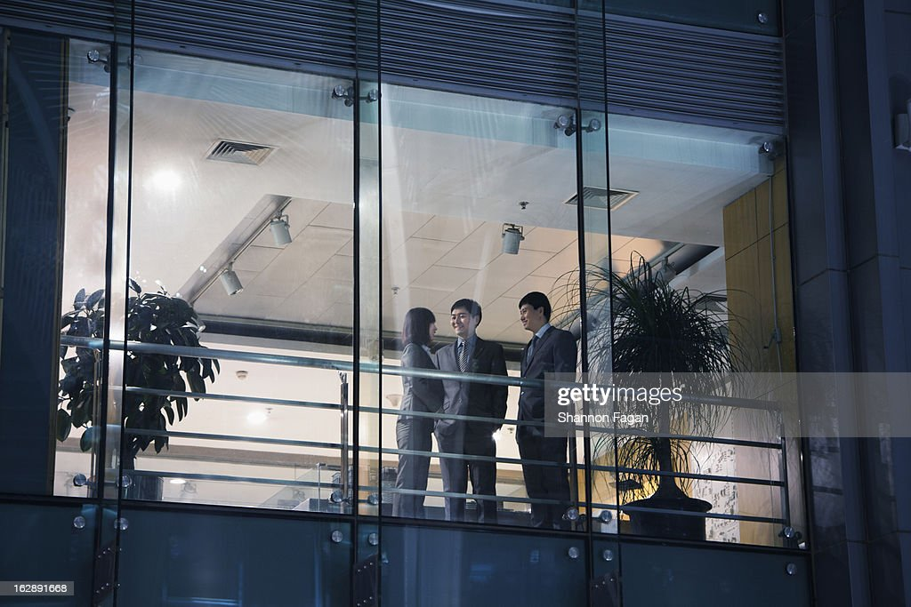 View of business people through a window at night : Stock Photo