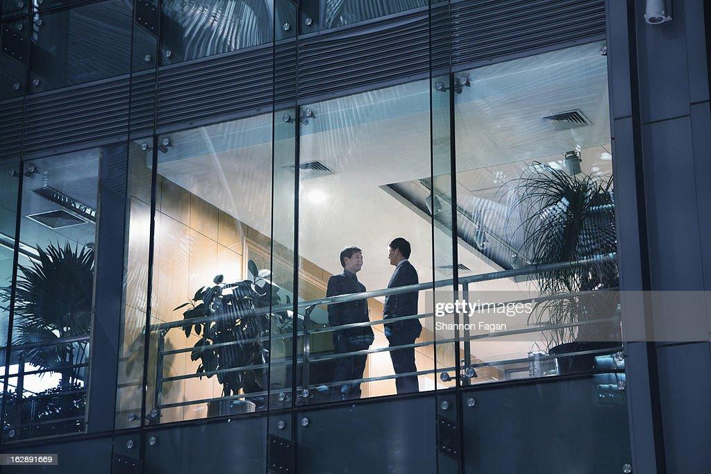 View of businessmen talking through a window : Stock Photo