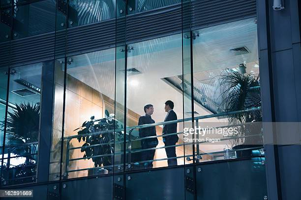 View of businessmen talking through a window