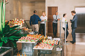 View of different canapes, tartlets and snacks on buffet table in restaurant. Business people eating and talking in background. Catering concept