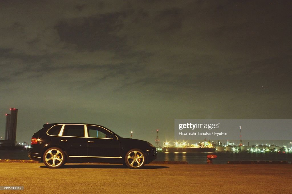 View Of Car By River At Night With City In Background