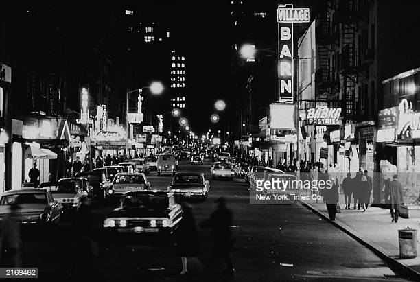View of cars and club marquees on Eighth Street at night looking east from Sixth Avenue in Greenwich Village New York City November 18 1965