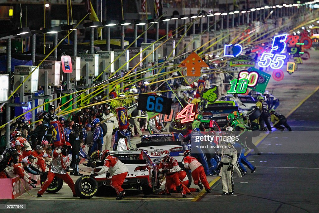 A view of cars pitting during the NASCAR Sprint Cup Series Bank of America 500 at Charlotte Motor Speedway on October 11 2014 in Charlotte North...