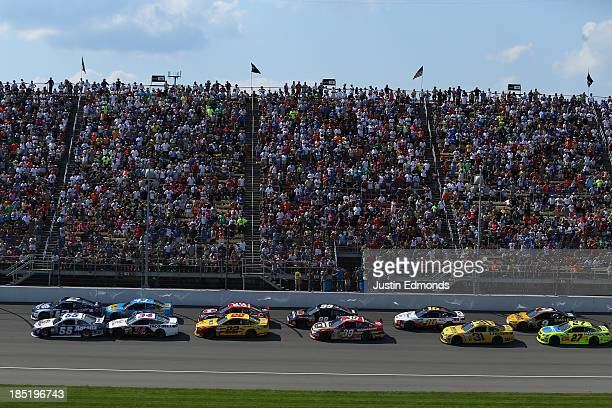 A view of cars racing during the NASCAR Sprint Cup Series 44th Annual Pure Michigan 400 at Michigan International Speedway on August 18 2013 in...