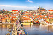 View of Charles Bridge, Prague Castle and Vltava river in Prague, Czech Republic from above. Nice sunny summer day with blue sky and clouds. Famous landmarks in Europe