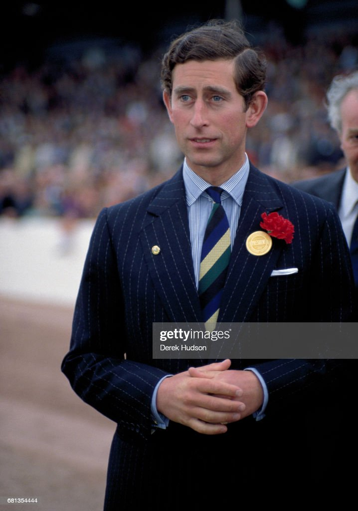 View of Charles, Prince of Wales, dressed in a chalk-stripe, single-breasted navy blue suit with a carnation in the lapel, as he attends the East of England Agricultural Show, Peterborough, England, early 1970s.