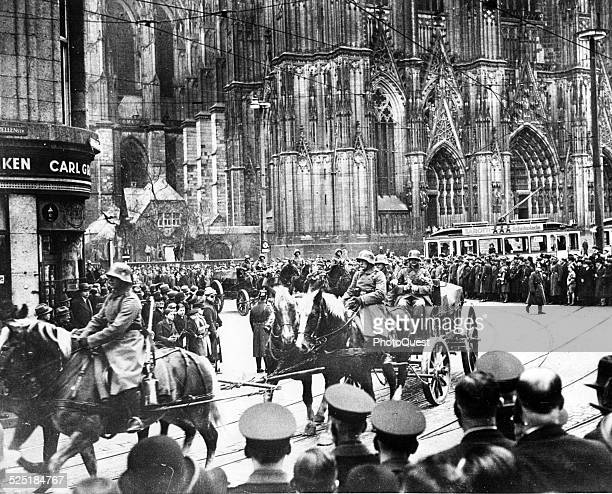 View of citizens as they crowd the streets as German Transport detachments parade through the streets in front of the Cathedral during the occupation...