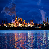 View of coastal oil refinery and smoke stacks at night