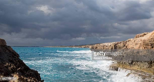 View of coastline and turbulent sea, storm sky