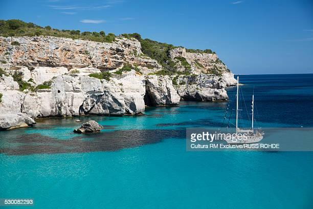 View of coastline and yacht, Cala Macarelleta, Menorca, Spain