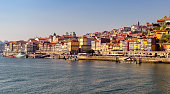 View of colorful buildings in Porto coastal Ribeira neighborhood and Douro river in Portugal.