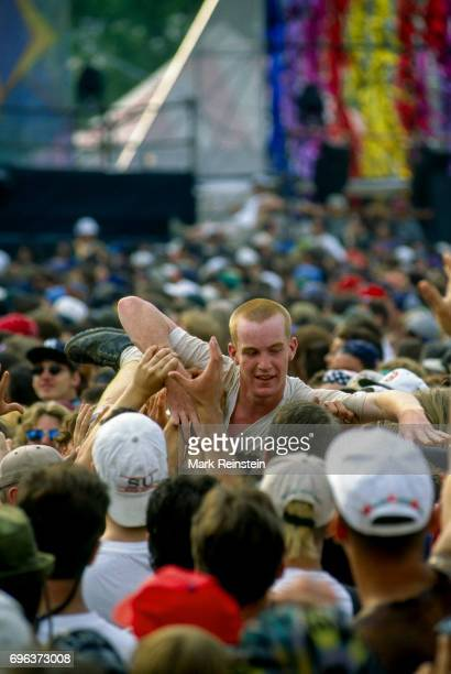 View of concertgoers one of whom crowd surfs in front of the main stage during the Woodstock '94 music festival at Winston Farms Saugerties New York...