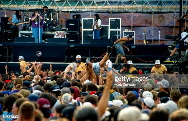 View of concertgoers several of whom crowd surf in front of the main stage during the Woodstock '94 music festival at Winston Farms Saugerties New...