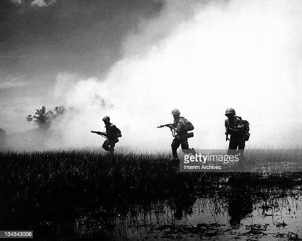 View of crack troops of the Vietnamese Army running across marshy terrain in Vietnam's delta country during operations against the Communist Viet...