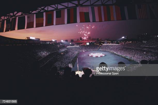 View of dancers and performers grouped in a circle around an olympic rings banner as fireworks are let off during the opening ceremony of the 1996...