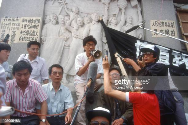 View of demonstrators gathered in Tiananmen Square where singercomposer Hou Dejian speaks through a megaphone also seen are literary critic Liu...