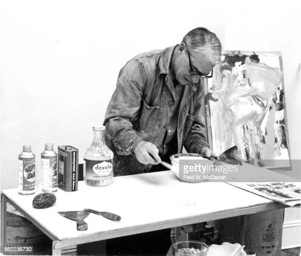 View of Dutchborn American artist Willem de Kooning as he mixes paint in his loft studio New York New York March 23 1962