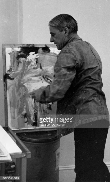 View of Dutchborn American artist Willem de Kooning as he works on a canvas in his loft studio New York New York March 23 1962