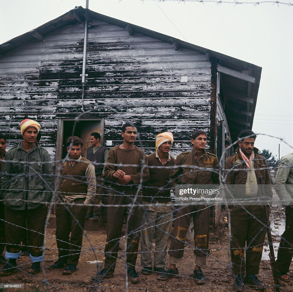 View of Egyptian prisoners of war standing behind a barbed wire fence, being held captive at the Atlit detainee camp near Haifa, Israel in December 1967 after the end of hostilities in the Six Day War between Israel and various Arab states.