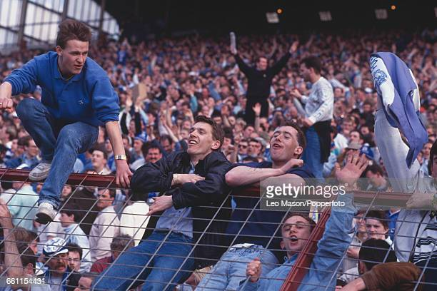 View of Everton fans climbing on and over crowd control fencing at Villa Park in Birmingham during the FA Cup semifinal between Everton and Norwich...