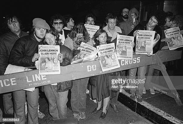 View of fans behind a police barrier outside the Dakota Apartments during a memorial vigil for murdered musician John Lennon New York New York...