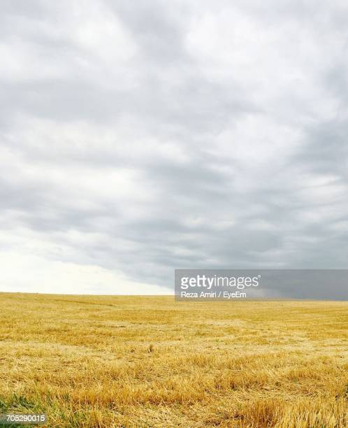 View Of Fields Against Cloudy Sky