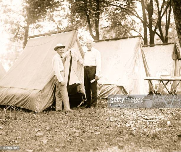 View of Firestone Tire Company founder Harvey Firestone standing next to President Warren Harding outside tents erected for their camping trip 1921