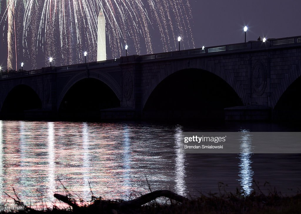 A view of fireworks above the Washington Memorial and Memorial Bridge on the National Mall in Washington DC from along the shore of the Potomac River...