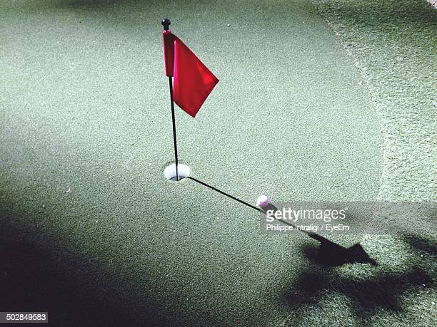 View of flag and ball on golf course