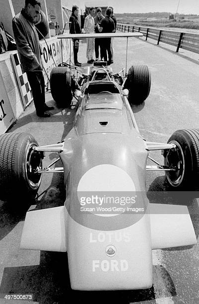 View of Formula One car in the pit area of a race track as its owner British racecar driver and team owner Graham Hill talks with a group of men...