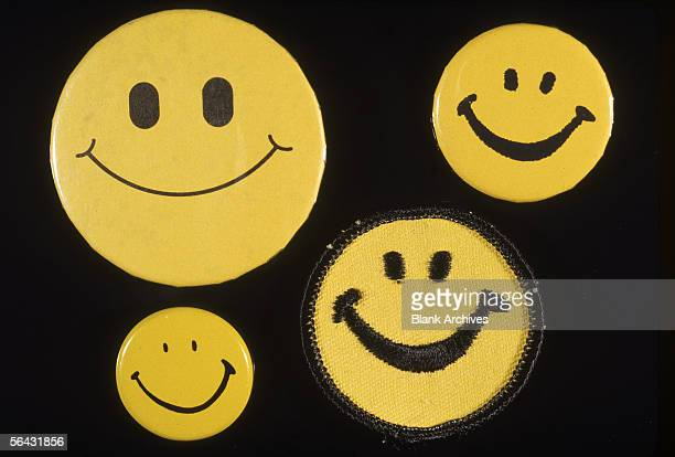 View of four differently styled Smiley face buttons 1970s