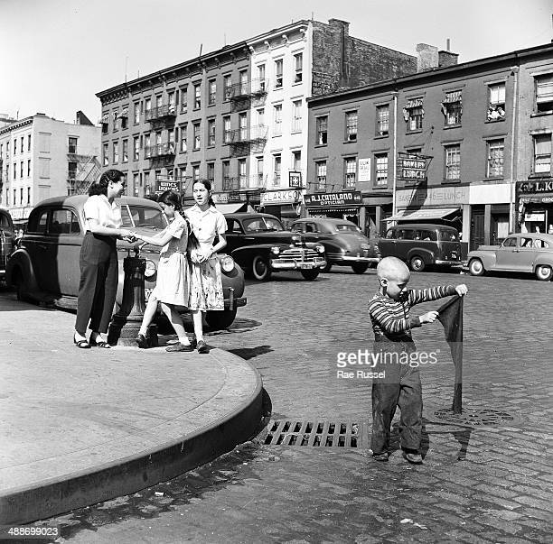 View of four young children three girls and a boy on an unidentified street corner Brooklyn New York New York 1949