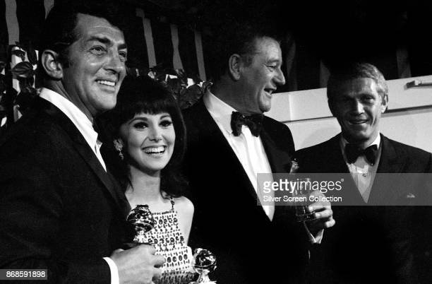 View of from left American actors Dean Martin Marlo Thomas John Wayne and Steve McQueen as they pose together at the 24th Annual Golden Globe Awards...