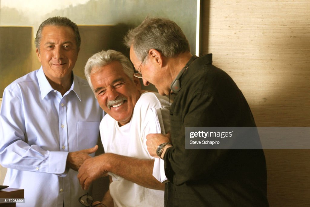 View of, from left, American actors Dustin Hoffman and Dennis Farina (1944 - 2013), and director Michael Mann share a laugh on the set of the pilot episode of the television series 'Luck', Los Angeles, California, 2011.