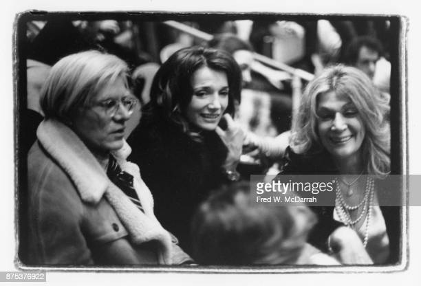 View of from left American Pop artist Andy Warhol socialite Lee Radziwell and actress Sylvia Miles as they attend a concert at Madison Square Garden...