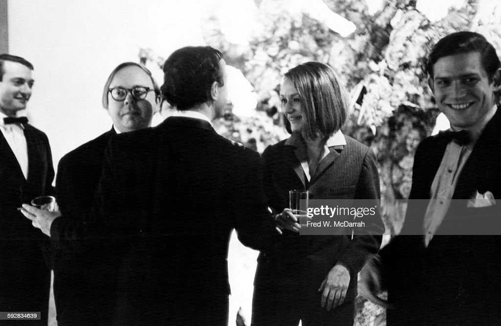View of, from left, American Pop artist Roy Lichtenstein (1923 - 1997), curator and critic Henry Geldzahler (1935 - 1994), author and critic Frank O'Hara (1926 - 1966) (back to camera), French artist Niki de Saint Phalle (1930 - 2002), and author and critic Bill Berkson as they attend a Parke-Bernet auction, New York, New York, April 14, 1965.