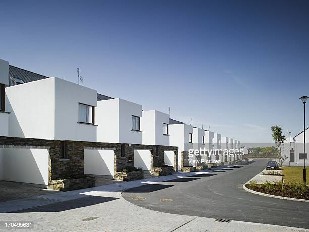 View of front facade of terrace from road leading to development entrance showing white render stone cladding and timber finishings Cluain Padraig...