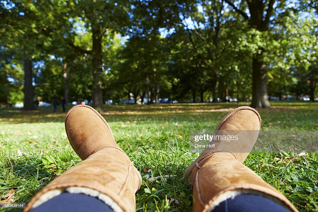 view of girls winter boots as she sits in grass in : Stock Photo