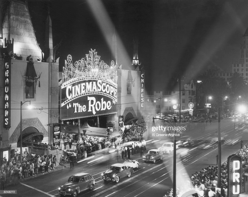 View of Grauman's Chinese Theater in Hollywood with floodlights shining and crowd standing in line at the premiere of director Henry Koster's film...