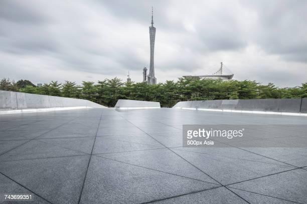 View of Guangzhou TV Tower behind trees against cloudy sky, Guangzhou, Guangdong, China