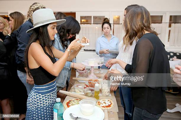 A view of guests preparing pizzas during host Katherine Schwarzenegger's Amazon Echo cooking class at AU FUDGE on August 4 2016 in West Hollywood...