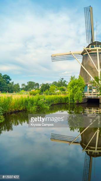 View of Half of Windmill reflecting in still canal