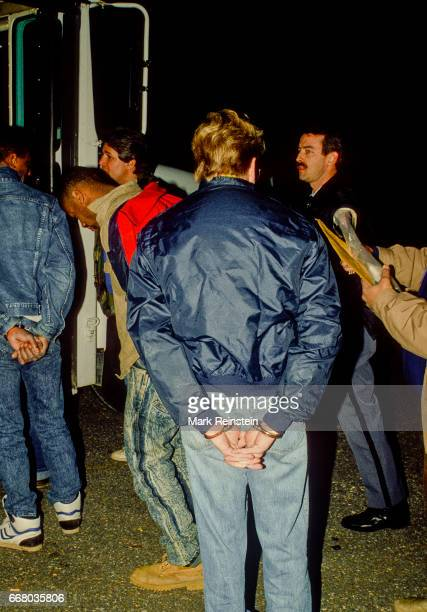 View of handcuffed suspects arrested during a crack cocaine drug bust as they are lined up by Prince George County police to board a prison bus...
