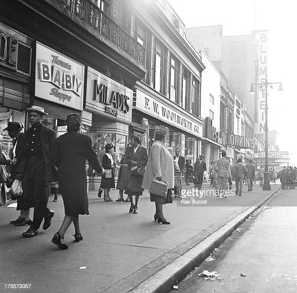 View of heavy pedestrian traffic and storefronts along 125th Street in Harlem New York New York 1948 Among the stores visible are Woolworth's and...