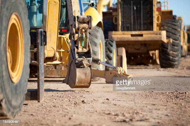 View of heavy road construction equipment on a dirt road
