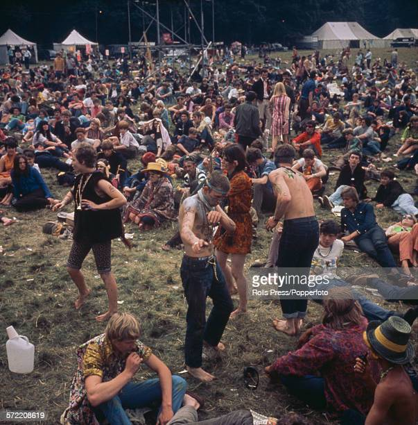 View of hippies and teenagers relaxing whilst dancing sitting and lying on grass in front of a stage at a 'LoveIn' at the Festival of the Flower...