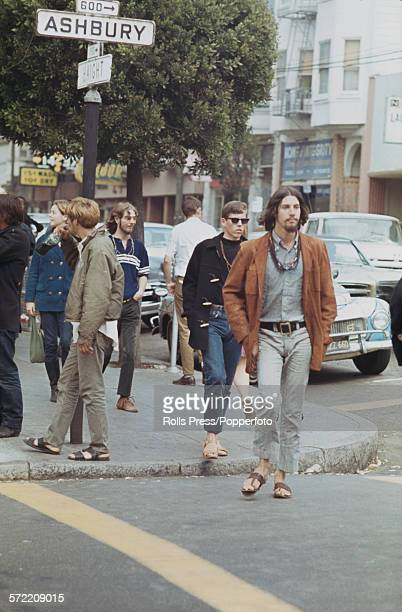 View of hippies and young people standing and walking across a sidewalk at the intersection of Haight and Ashbury streets in the HaightAshbury...